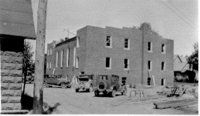 Construction vehicles in front of a partially completed brick church.